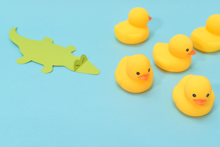 Defeat concept, rubber ducks are chased by crocodile. Banco de Imagens