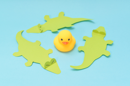 Trap concept, rubber duck is surrounded by crocodiles. 版權商用圖片
