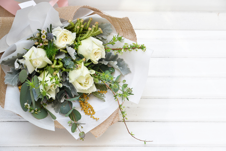 White roses bouquet on wooden floor