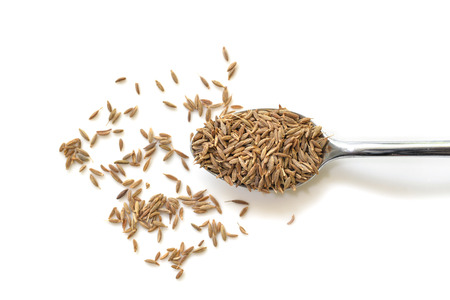 Cumin seed in a spoon on white background from top view