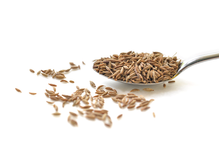 Cumin seed in a spoon on white background