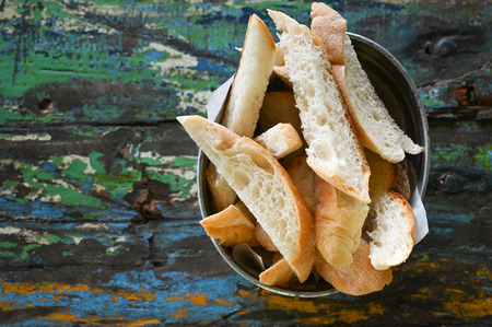 Toasted bread in a bucket on old wooden table