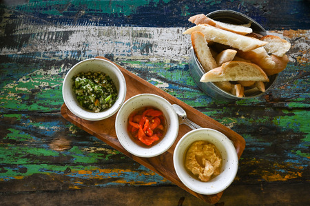Variety of dips with bread on old wooden table