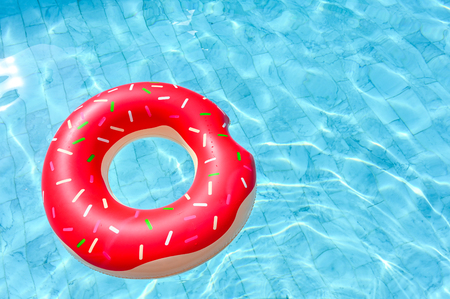 Donut shape, floating rubber ring in the swimming pool Imagens