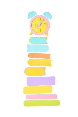 Stack of books with alarm clock paper cut on white background - isolated