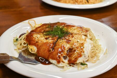 Okonomiyaki on white plate, Japanese food 写真素材