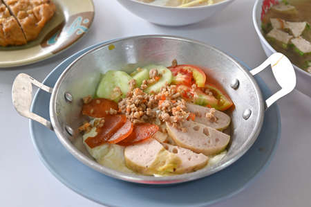 Breakfast with fried egg in a pan top with mince pork and local sausages - Thai northeastern style food