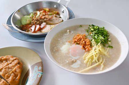 Breakfast with congee, egg and local sausage - Thai northeastern style food