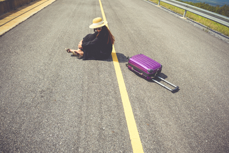 take a history: Women dressed in black with purple travel wallet,Traveling by road. Stock Photo