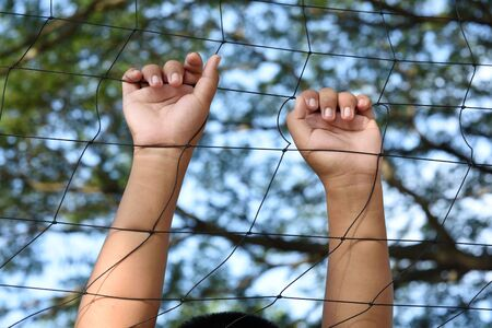 cell block: Hands with rope mesh fence