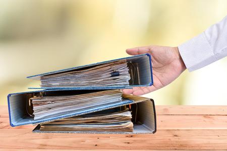 een bestandsmap met documenten en belangrijk document, op een houten achtergrond