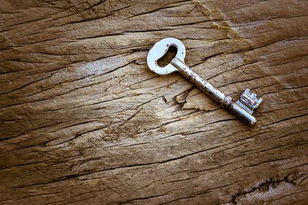glisten: key on old wood background Stock Photo