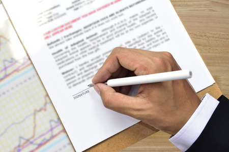 businessman signing documents: Businessman signing documents,with White pen on wooden desk.