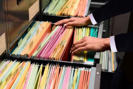 Handen Zakenman zoeken via bestand mappen met personal finance documenten Stockfoto