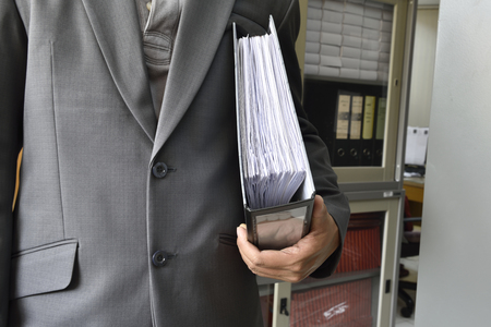 personal finance: Hands Businessman searching through file folders with personal finance documents