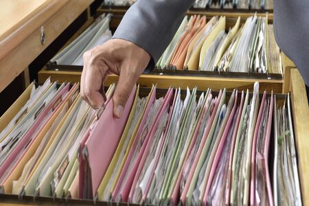 categorize: Hands Businessman searching through file folders with personal finance documents