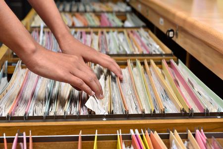Hand vrouw op zoek naar documenten in het kabinet Stockfoto