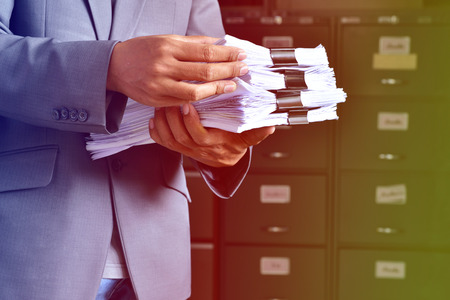 gestion documental: document management,Businessman examining documents