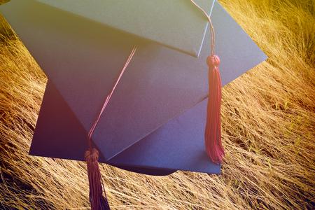 toga y birrete: Casquillo, el vestido se grad�a en el fondo de hierba Foto de archivo