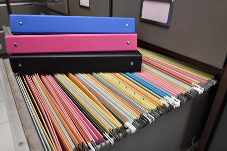 Files placed on a metal filing cabinet. Banco de Imagens