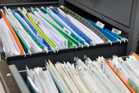Files placed on a metal filing cabinet. Archivio Fotografico