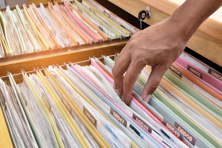 Hand of the employee search Financial documents stored in filing cabinets. Archivio Fotografico