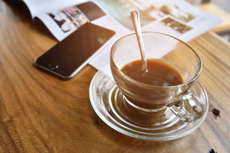 coffe cup and smartphone pace on wood desk in office