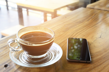 pace: coffe cup and smartphone pace on wood desk in office