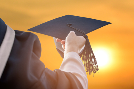 Graduates hold a hat during the sunset. Stock Photo
