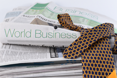 Stack headline business newspaper and necktie on white isolated background.