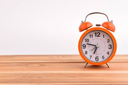 Orange alarm clock on wooden floor, white backdrop Stock Photo