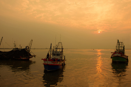 Fisherman are leaving out for fish in the evening whlie the sunset. Stock Photo