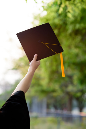 Behind photo of university graduate wears gown and black cap, yellow ribbon and blur bokhe background.