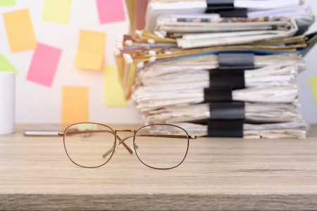 stack documents and back paper clip pace on wood desk in office.