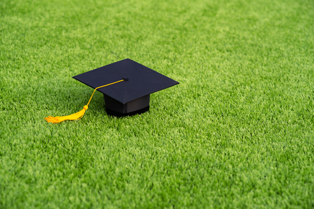 Graduation Black hat and yellow tassel pace on Green field Banque d'images