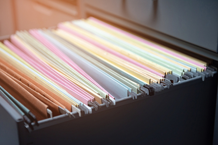 Colorful business documents are placed in a filing cabinet in the office. Stok Fotoğraf