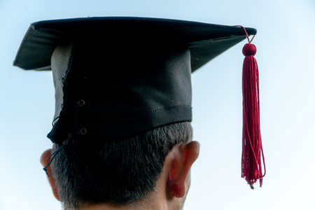 Back portrait of graduated wearing a black hat. Stok Fotoğraf