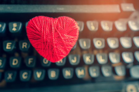Red heart placed on an old typewriter