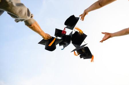 Lanza un sombrero negro de graduados al cielo.
