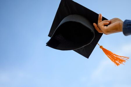 Graduates hold a black hat with a yellow tassel attached to the sky. 版權商用圖片