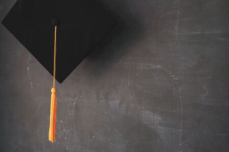 Black graduates hat hung on the blackboard