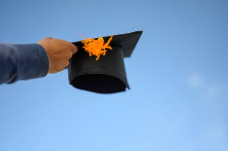 Graduates hold a black hat with a yellow tassel attached to the sky.