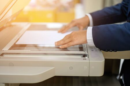 Employees are copying documents with a copy machine at the office. Standard-Bild