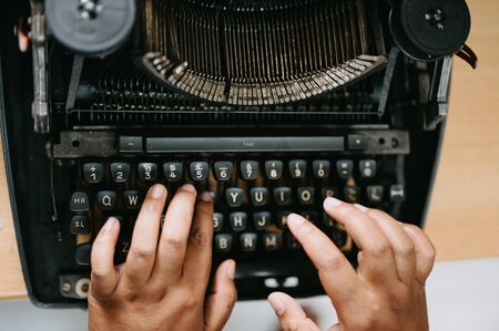 Hands placed on Old black typewriter