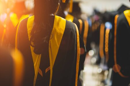 Graduates receive a certificate at a university diploma ceremony.