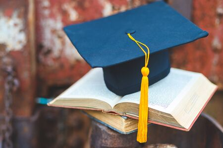 Black graduates hat and yellow tassel place an old book Banco de Imagens