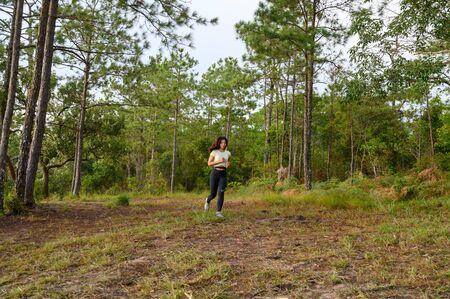 A woman running trek at a mountain pine forest. Zdjęcie Seryjne