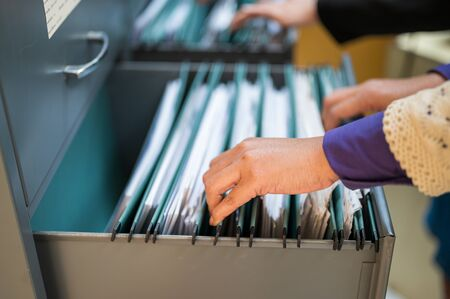 Employees use their hands to search documents in file cabinets.