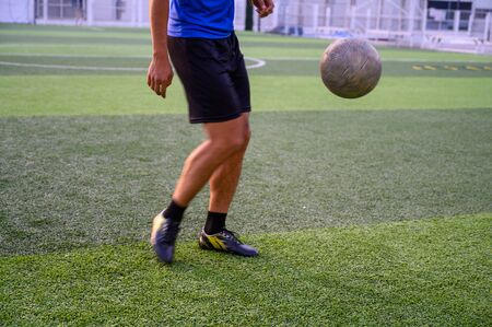 A male football player playing football on the green lawn