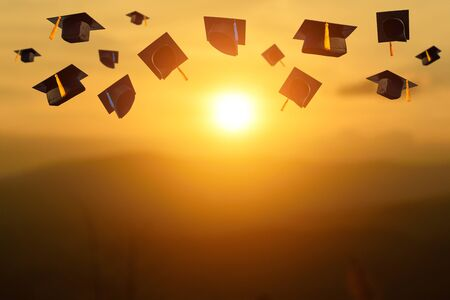 The students holding a shot of graduation cap by their hand in sunset during ceremony success graduates at the University, Concept of Successful Education in Hight School,Congratulated Degree